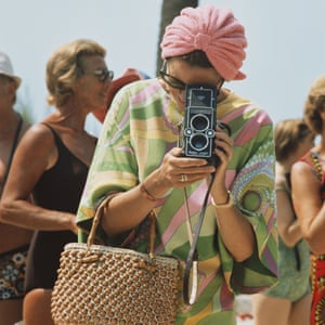 Princess Grace of Monaco taking a photograph at a swimming competition at Palm Beach, Monte Carlo, wearing a Pucci kaftan and matching turban.