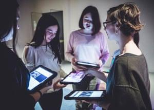 Teenage girls in a circle looking at iPads