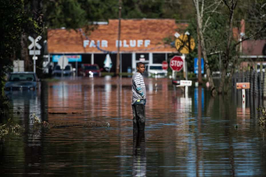 Austin Snowten stands in a flooded street caused by remnants of Hurricane Matthew on October 11, 2016 in Fair Bluff, North Carolina.
