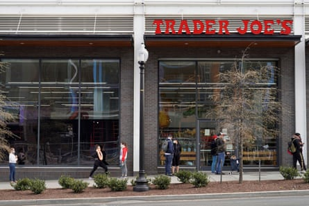 People maintain social distancing as they wait to enter a Trader Joe's grocery store.