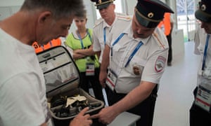 Security officials search a photographer's equipment bag inside the Volgograd Arena on Saturday.