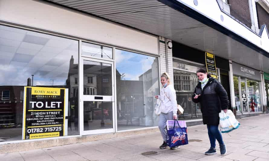 Shoppers walk past empty shops in Newcastle-Under-Lyme, England.