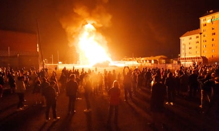 People watch a bonfire in the Sandy Row area ignite after it is lit by petrol bombs during the 12 July celebrations.