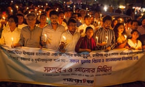 People march behind a banner at a protest against the killing of atheist bloggers and publishers in Dhaka