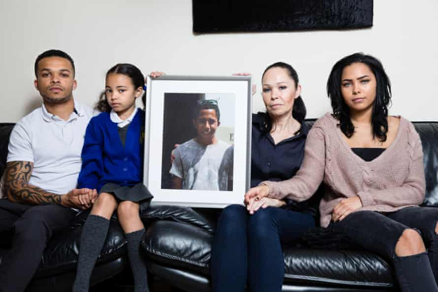 Tracey Rogers (second right); her son Nathaniel, 27 (left); daughter Holly, 20 (right); and daughter Macey, 9, (second left), with a photo of Tracey's son Jerome.