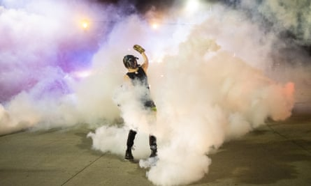 Protester holds a smoke canister during a night of clashes between protesters and Detroit police officers Saturday night.