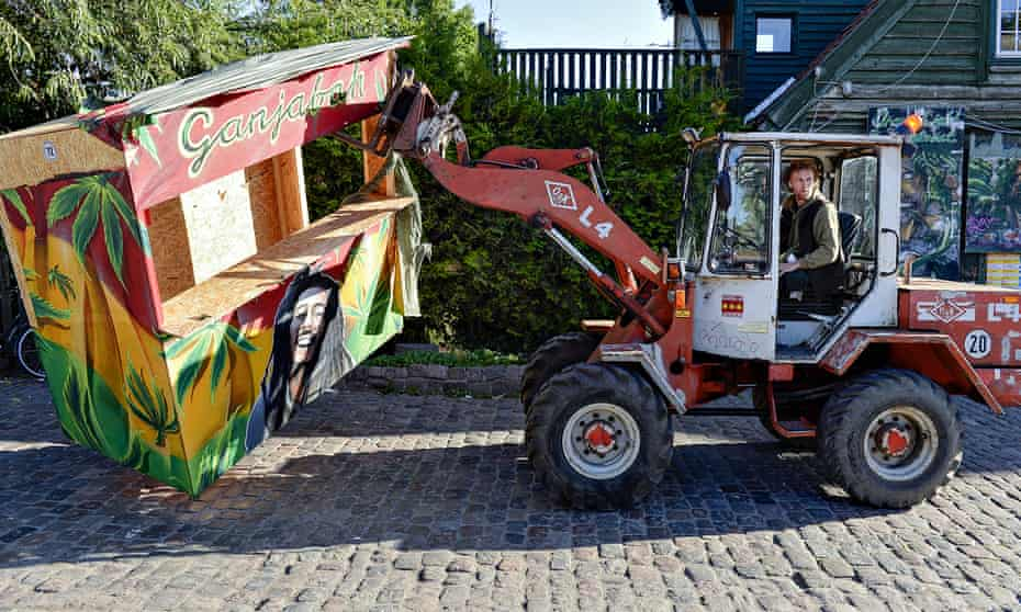 A Christiania resident removes a hash stall from Pusher Street, where up to 1bn krone changes hands every year.