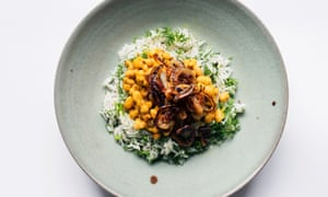 A round earthy green plate with rice and dill and bean mixture on top