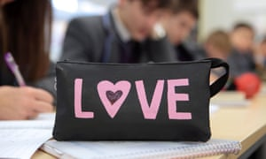 A pencil case with the word 'love' sits on a school pupil's desk.