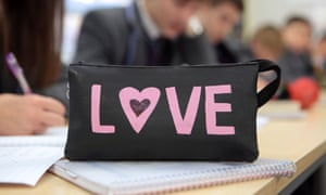 Children in a classroom behind a pencil case with LOVE on the side