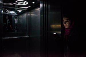 During a blackout a girl waits by a elevator for the power from her family's generator to operate it