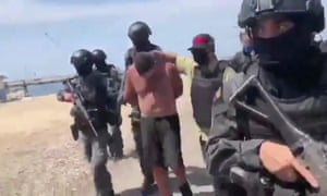 Venezuelan soldiers in balaclavas move a suspect from a helicopter after what Venezuelan authorities described as a 'mercenary incursion'