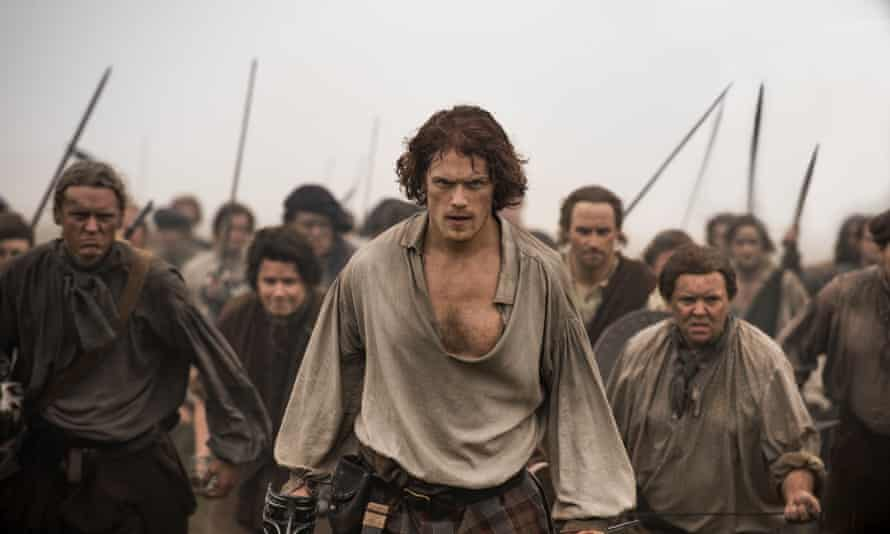 Sam Heughan and some extras carrying swords