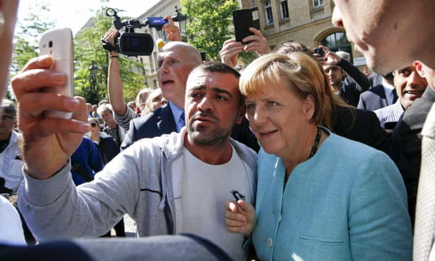 A man takes a selfie with the German chancellor, Angela Merkel, outside a refugee camp in Berlin.