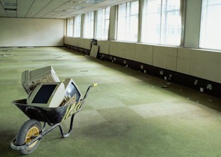 Wheelbarrow and computer monitors in empty office