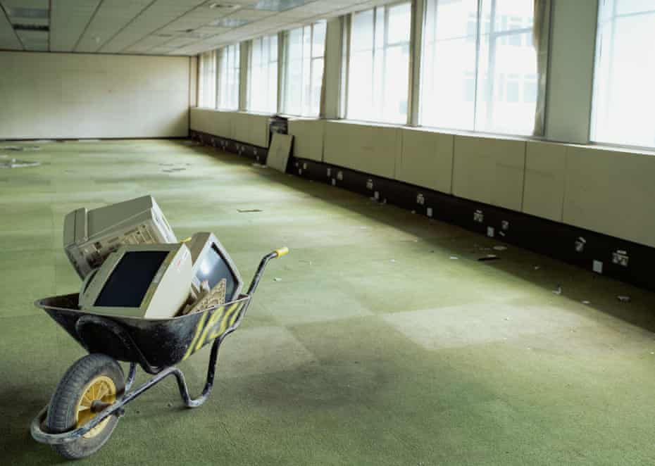 Wheelbarrow and computer monitors in empty office