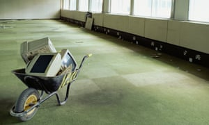 Wheelbarrow and computer monitors in office