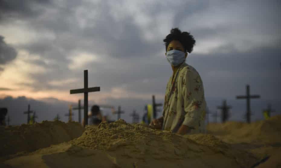 A protester digs a mock grave on Copacabana beach symbolizing deaths due to the coronavirus, in Rio de Janeiro.