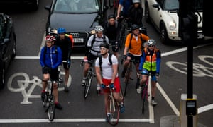Cyclists wait for a traffic light to change.