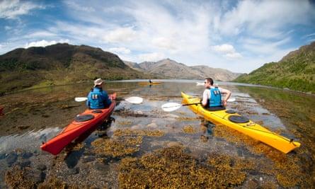 Two men kayaking in a loch, Scotland