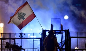 An anti-government protester waves a Lebanese flag during clashes with police outside parliament.