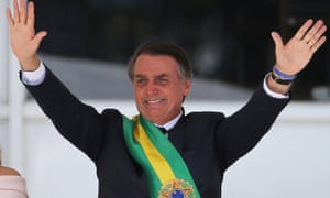 Jair Bolsonaro gestures to crowds after receiving the presidential sash from outgoing President Michel Temer at the Planalto Palace, in Brazil on 1 January 1, 2019.