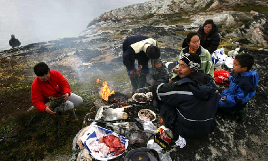 An Inuit fisherman and his family have a seal meat barbeque.