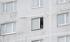 A man seen in a window of an apartment block in the Kurkino district of Moscow