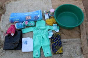 Merina's bag: bowl, baby clothes and socks, hat, nappies, towel, tissues, cotton wool, wrapper, clothes, talcum powder, cream