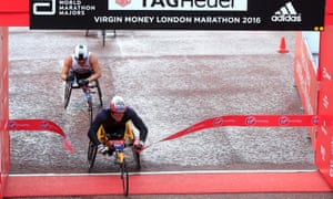 Marcel Hug breaks the tape to win the men's wheelchair race, ahead of Kurt Fearnley and Dave Weir.