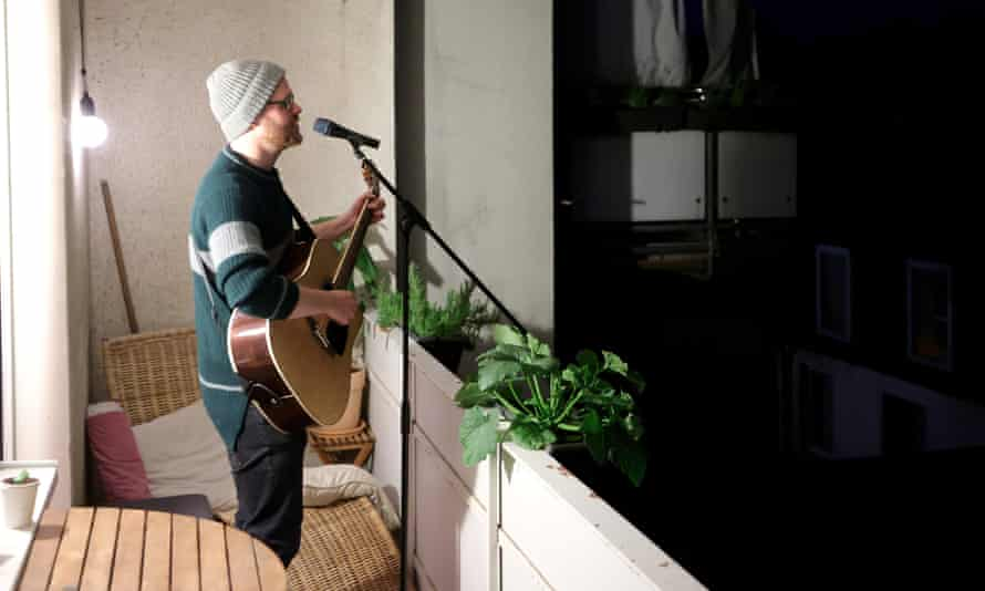 Thorsten Schmidt performs on the balcony of a house in Dortmund. Balkonsänger (balcony singer) is one of 1,200 new German words related to the pandemic.