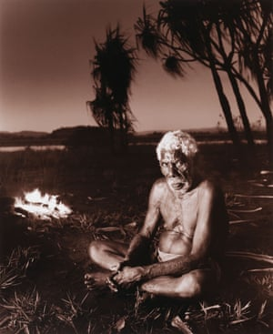 Man sits on Country with a fire behind him