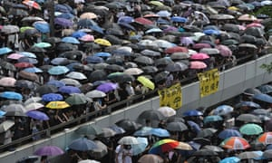 Protesters shelter under umbrellas during a downpour as they occupy roads near the government headquarters in Hong Kong.
