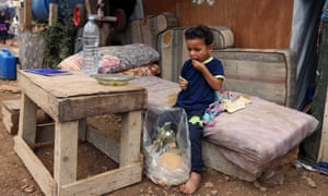 A Syrian boy eats in front of his family tent at a refugee camp near Sidon, Lebanon.