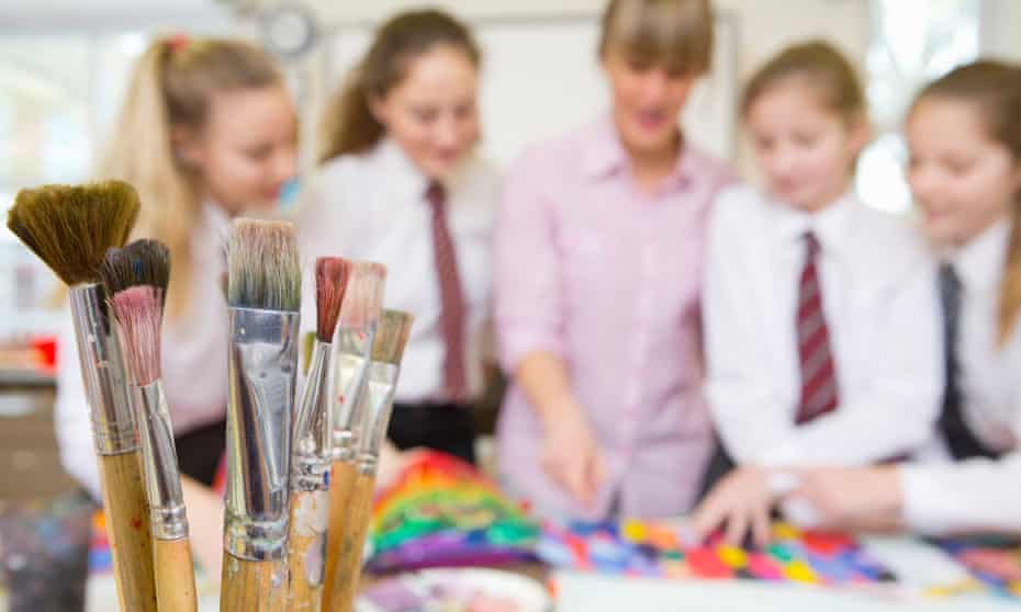 Paintbrushes with blurred-out children in background