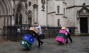 Documents are pushed to the Royal Courts of Justice last week