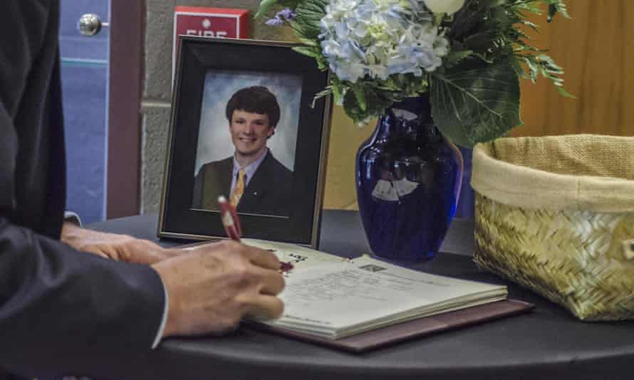A mourner signs a guest book at Wyoming high school in Ohio during the funeral of Otto Warmbier.