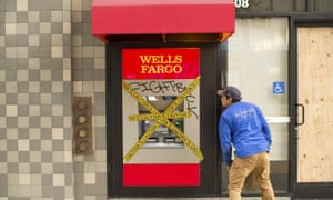 A clean-up worker examines damage to a Wells Fargo branch the morning after May Day protests.