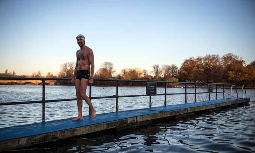 A member of the Serpentine Swimming Club leaves after enjoying an early morning swim in Serpentine Lake in Hyde Park in London.