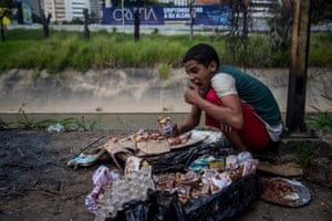 Jesus eats something he found in a garbage bag in Las Mercedes.