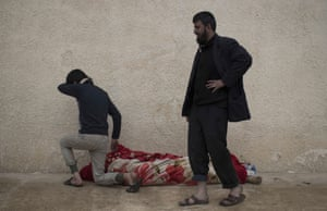 Relatives next to the body of Suheyil Najn Abdullah after he was killed by a sniper while trying to flee fighting between Iraqi security forces and Isis