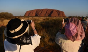 Tourists take photos of Uluru