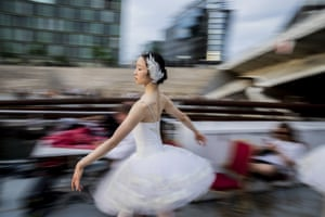 A dancer from the Berlin State Ballet performs Swan Lake on an excursion boat during a tour of the city centre