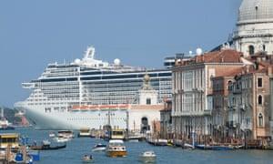 An enormous cruise ship sails through Venice