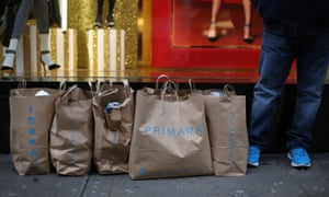 Customers wait with their purchases outside Primark