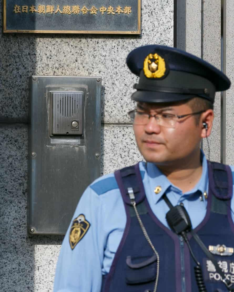 A police officer at the pro-Pyongyang General Association of Korean Residents in Japan building. There are fears of protests and violence from people angry after a North Korean missile flew over Japan.