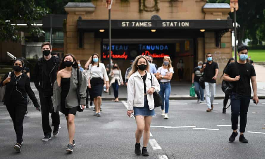 Commuters wearing face masks exit St. James Station in Sydney, Australia, 4 January 2021.