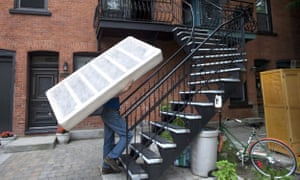 Jim Hendry carries a bed base up a set of stairs in Montreal on Moving Day. The day is no longer law, but remains as a rather problematic tradition.