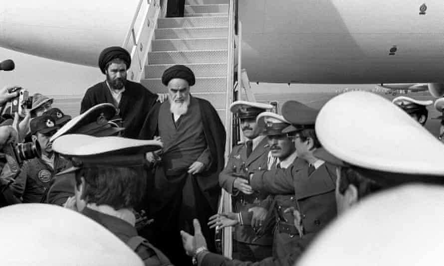 The Ayatollah Ruhollah Khomeini is welcomed at Tehran airport on 1 February 1979 on his return from exile in France.