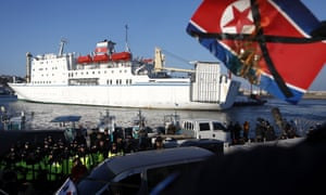 Activists burn a North Korean flag as part of the country's Olympic delegation arrives in South Korea by ferry.